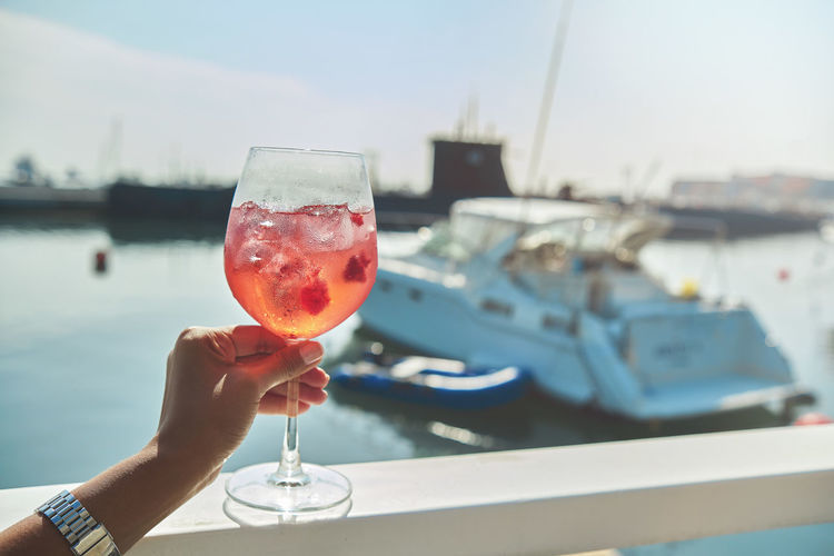 Close-up of hand holding wine glass against boat