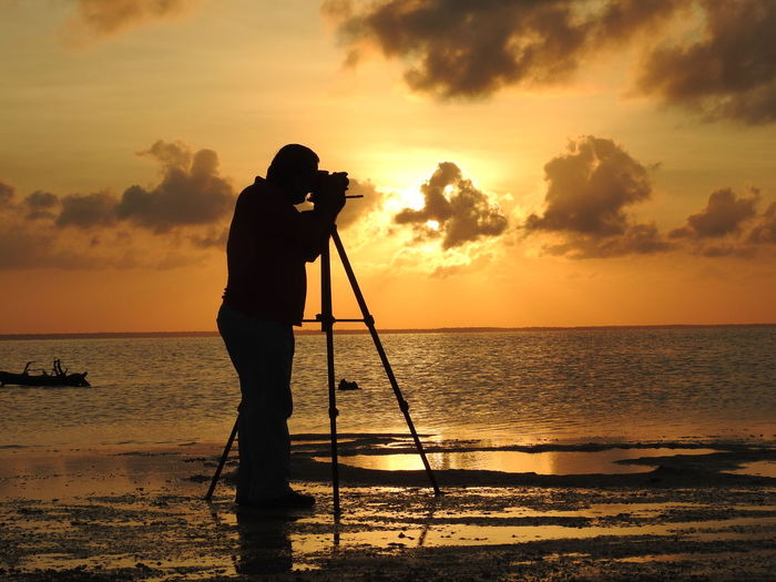 Silhouette Man Photographing At Beach Using Camera Against Sky During Sunset