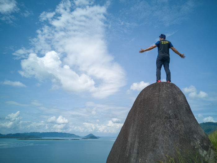 A man standing at the historical stone and facing stunning view of the ocean at the peak of Sirongol Hill in Semporna, Sabah, Malaysia. Sirongol Hill Adventure Sportsman Trekking Hiking Sky Cloud - Sky Scenics - Nature Beauty In Nature Day Water Outdoors One Person Standing Full Length Leisure Activity Lifestyles Sea Nature Real People Casual Clothing Rock Rear View Limb Human Arm Arms Outstretched Freedom
