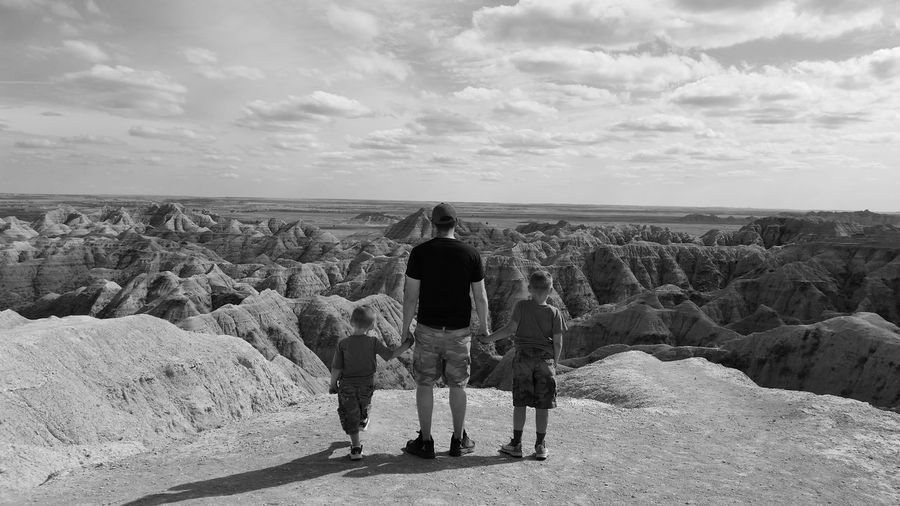 Rear View Of Father With Sons On Rock Formation Against Sky