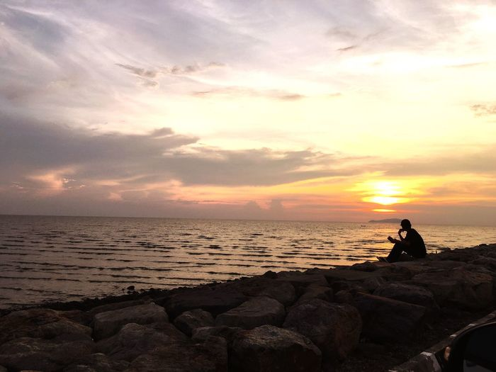 Silhouette man sitting on rocks by sea against sky during sunset