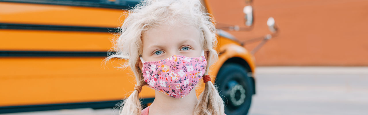 Portrait of cute girl wearing mask standing outdoors