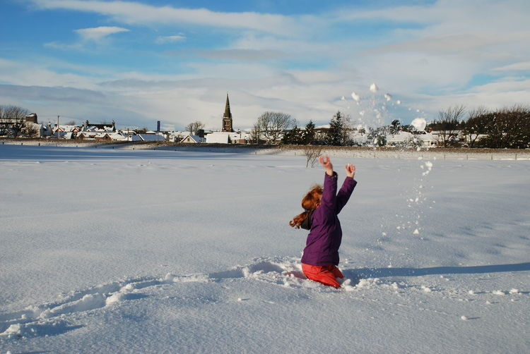 Teenage girl playing with snow against sky