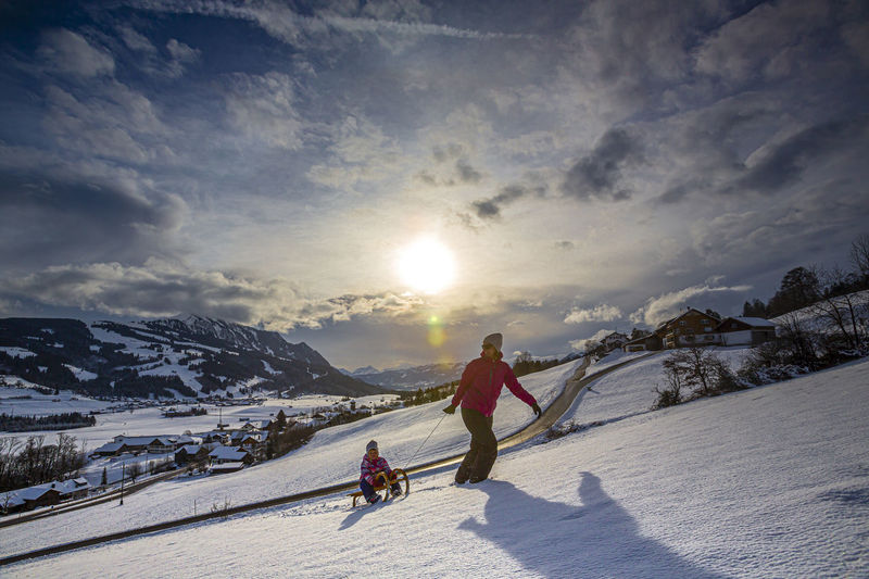 People skiing on snowcapped mountain against sky during winter