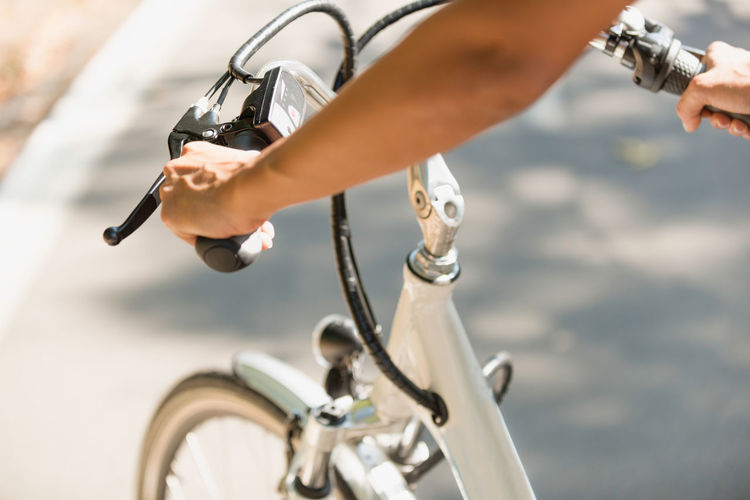 Cropped hands of woman holding bicycle handlebar