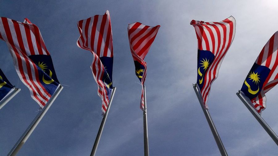 Low angle view of malaysian flags on poles