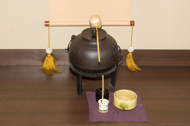 Close-up of japanese tea maker on floor against wall