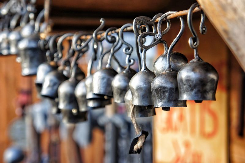 Close-Up Of Bells Hanging From Metal Rod At Market