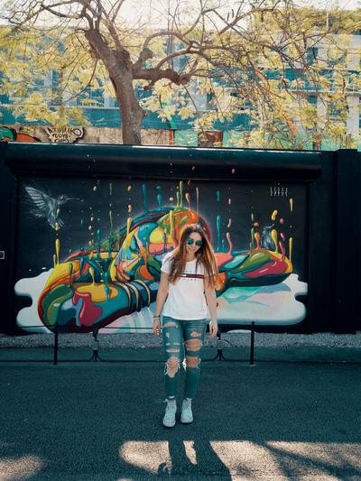 Full length of woman standing against graffiti