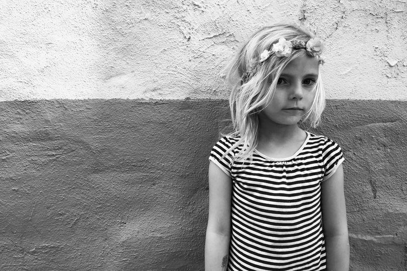 Portrait of cute girl wearing tiara against wall