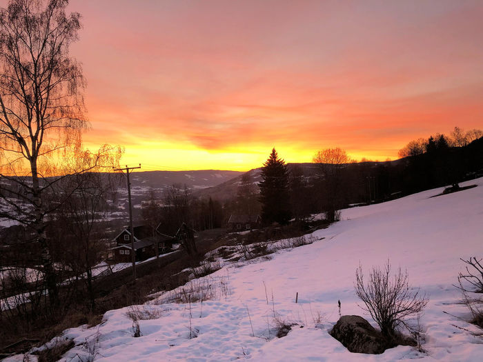 Scenic view of snow covered landscape against sky during sunset