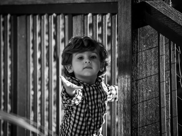 Portrait Of Cute Baby Boy Standing By Railing