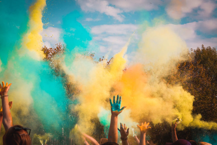 People playing with powder paints against sky