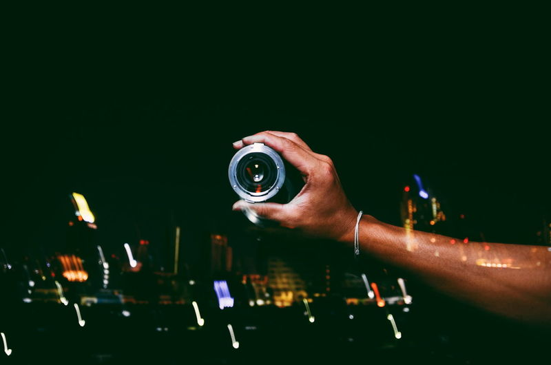 Double Exposure Of Cropped Hand Holding Lens With Cityscape