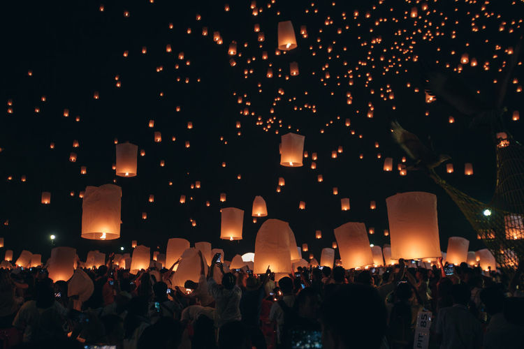 Crowd of people holding illuminated lanterns against sky at night