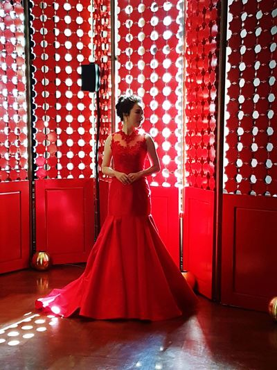 Model Wearing Red Evening Gown While Standing Against Wall