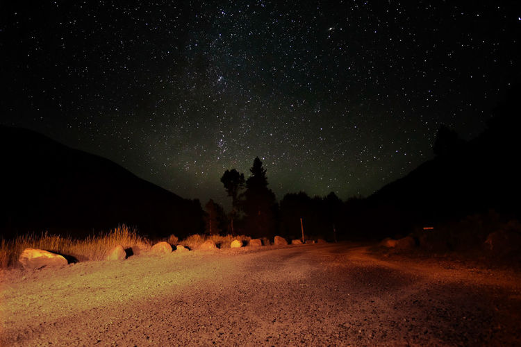 dirt road against star field in sky at night