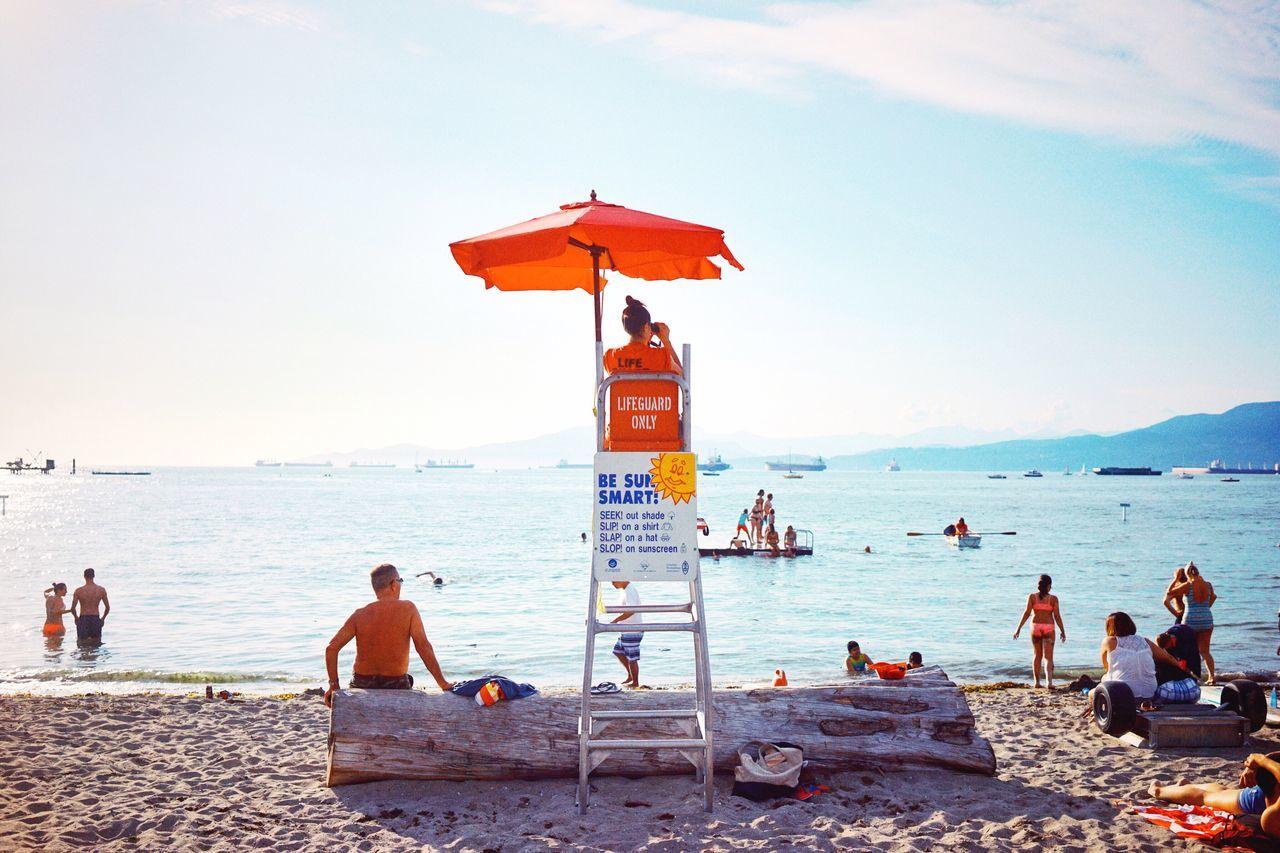 PEOPLE ON BEACH AGAINST SEA