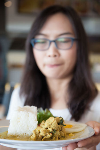 Close-up of woman holding food in plate at home