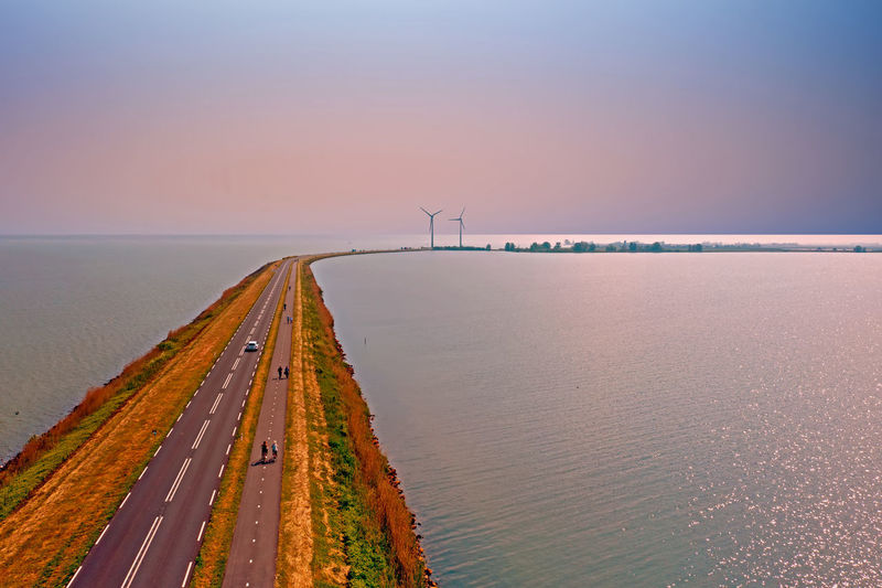 Scenic view of road in sea against sky during sunset