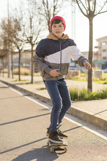 Hat Skateboarding Sunlight Architecture Building Exterior Built Structure Casual Clothing Day Focus On Foreground Front View Full Length Hooded Shirt Leisure Activity Lifestyles Looking At Camera One Person Outdoors Portrait Real People Sky Standing Streetphotography Tree Young Adult Young Women