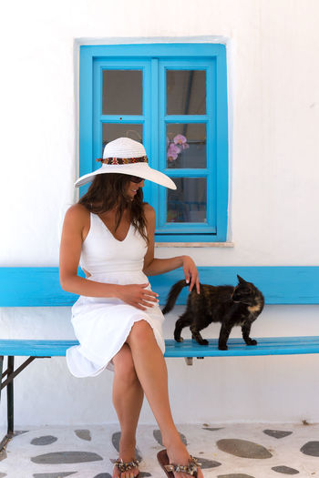 The Lady in white and the cat, Mykonos, Greece Bench Blue Casual Clothing Cat Classic Day Elegant Fashion Greece Greek Hat Lady Lifestyles Mykonos One Person Pets Postcard Real People Sitting Summer White Window Woman Young Adult