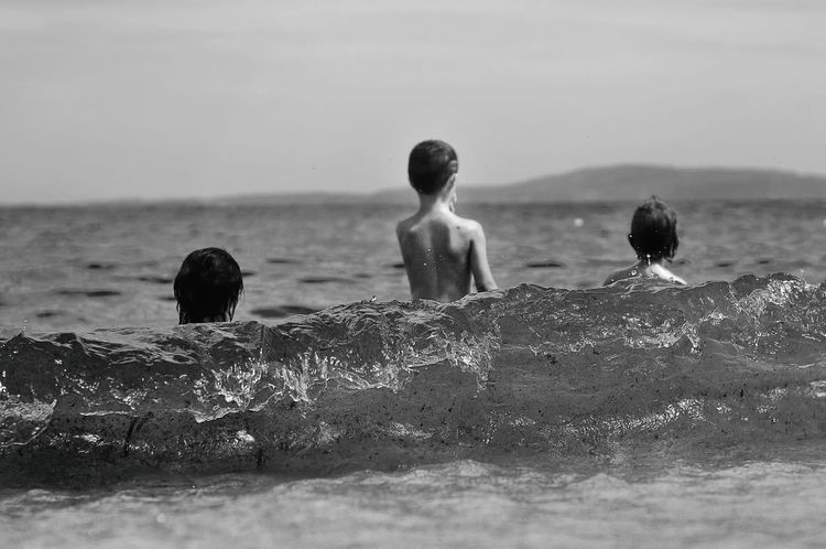 Enjoying the sea waves. Back View Backside Backside Portrait Black And White Bnw Childhood Memories Enjoy Enjoying The Sea Flashback Joy Looking For Looking Forward Memories Open Sea Sea Sea Wave Shirtless Togetherness Wave Waves