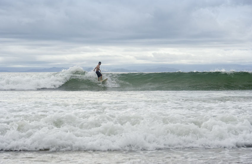 Young man surfing in Punta Leona, Costa Rica Adventure Balance Beach Board Costa Rica Extreme Sports Full Length Motion One Man Only One Person One Young Man Only Pacific Ocean Punta Leona Puntarenas Sea Skill  Sport Standing Surf Surfboard Surfing Swimwear Water Wave Young Adult