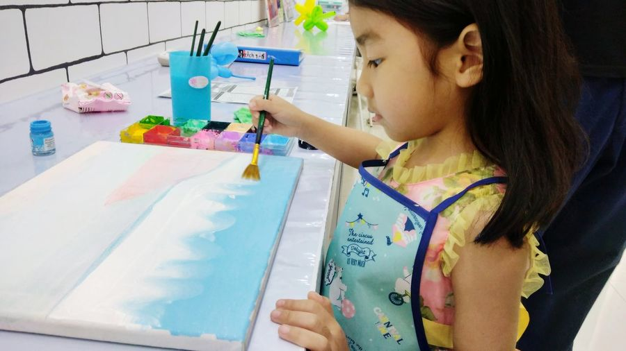 The girl is learning to paint the pictures of the sea