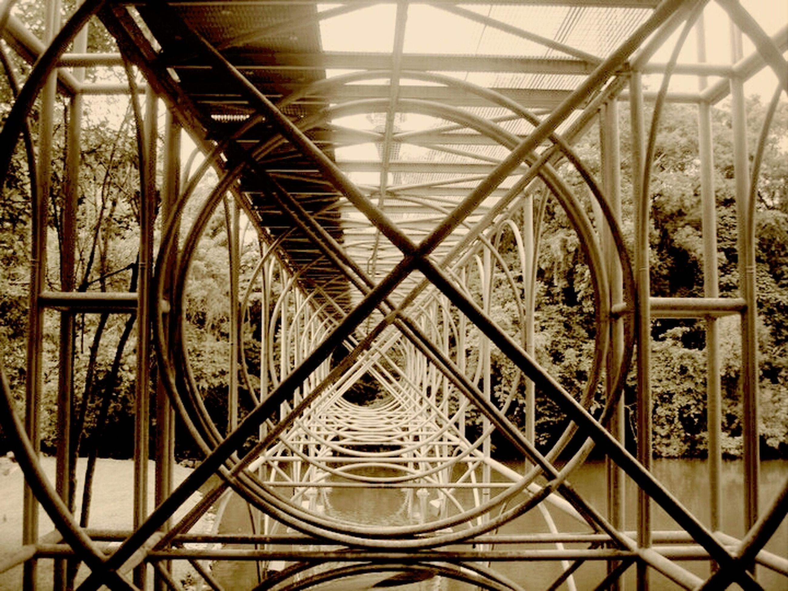 built structure, architecture, metal, indoors, metallic, bridge - man made structure, engineering, transportation, connection, low angle view, railing, pattern, no people, arch, day, diminishing perspective, travel, architectural feature, design, iron - metal