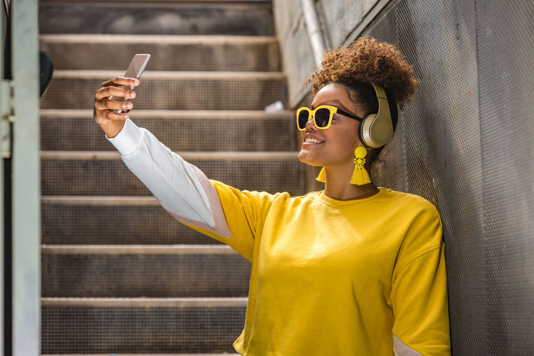 Smiling young woman taking selfie while listening music on mobile phone against wall