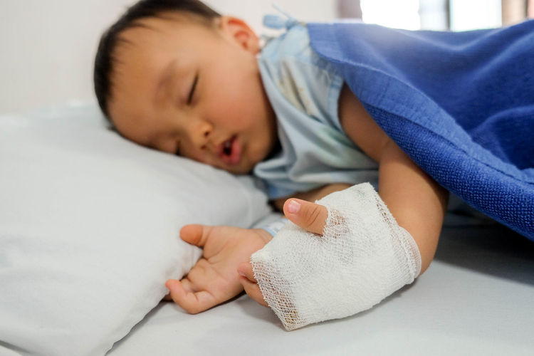 Injured boy sleeping on bed at home