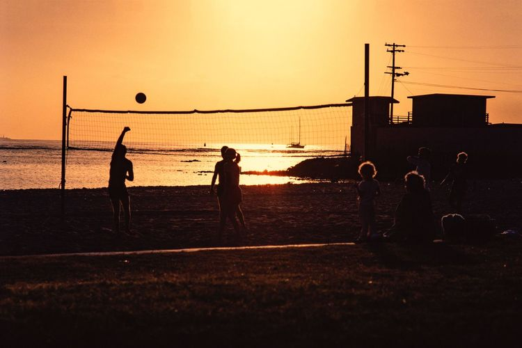 Silhouette people playing with ball on beach against sky during sunset