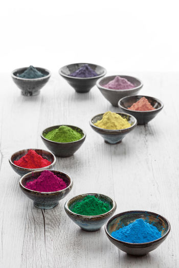 Colorful Holi powder gradually fading towards the background. Creative concept. Bowl Close-up Colorful Day Freshness Holi Powder Indoors  Multi Colored No People Powder Powder Paint Studio Shot Variation