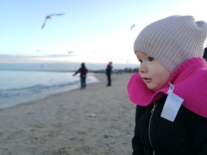 Close-Up Of Cute Girl Standing At Beach During Winter