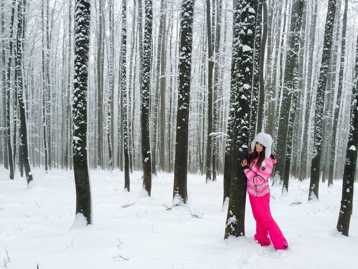 Smiling Woman Standing While Holding Tree Trunk In Snow Covered Forest
