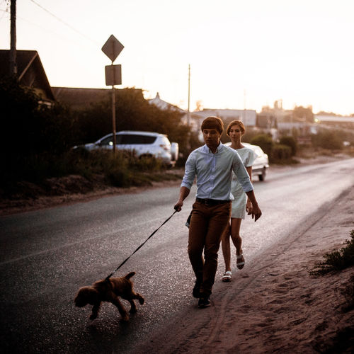 Rear view of man and dog walking on street