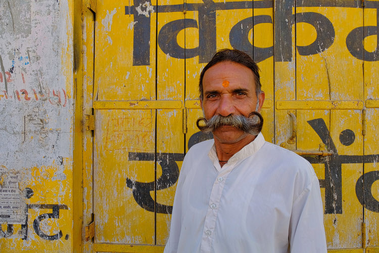 Local people of Mandawa, India. Mandawa, Rajasthan Adult Day Facial Hair Front View Lifestyles Looking At Camera Males  Mandawa Mature Adult Mature Men Men Mustache One Person Portrait Real People Senior Adult Standing Text Wall - Building Feature Western Script Yellow