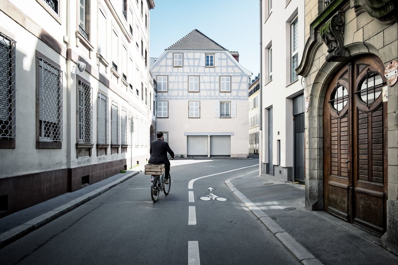 Rear view of man riding bicycle on road amidst buildings