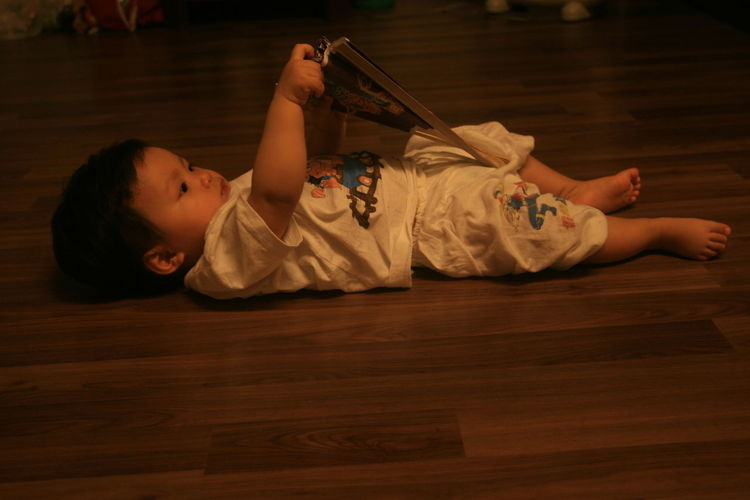 Baby playing with hand fan while lying on floor