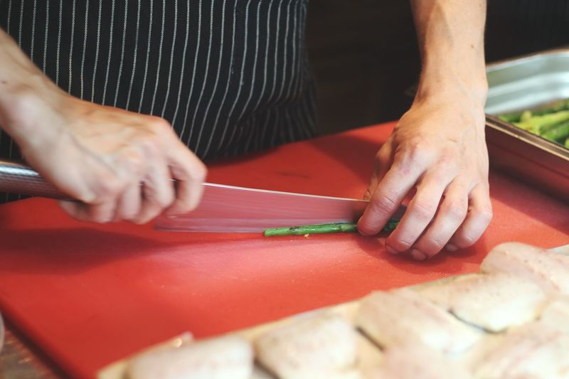 High Angle View Of Person Cutting Asparagus