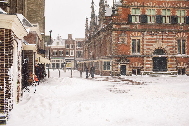 Snow covered street by buildings in city