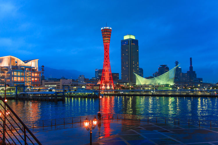 Illuminated Buildings By River In City Against Sky