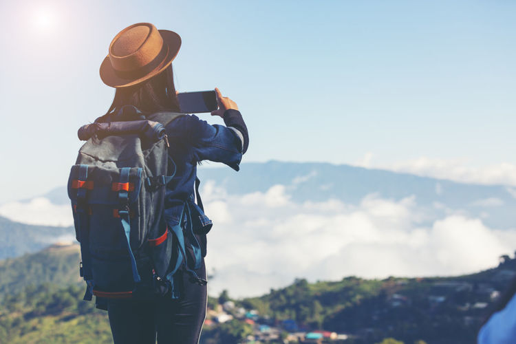 Hat Real People One Person Clothing Three Quarter Length Rear View Standing Sky Leisure Activity Lifestyles Photography Themes Activity Mountain Technology Nature Photographing Women Day Beauty In Nature Outdoors Looking At View Digital Camera