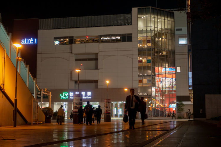 People walking on illuminated street amidst buildings at night