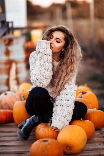 Thoughtful young woman sitting on pumpkins during halloween