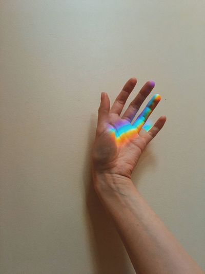 Cropped hand of person with multi colored light against wall