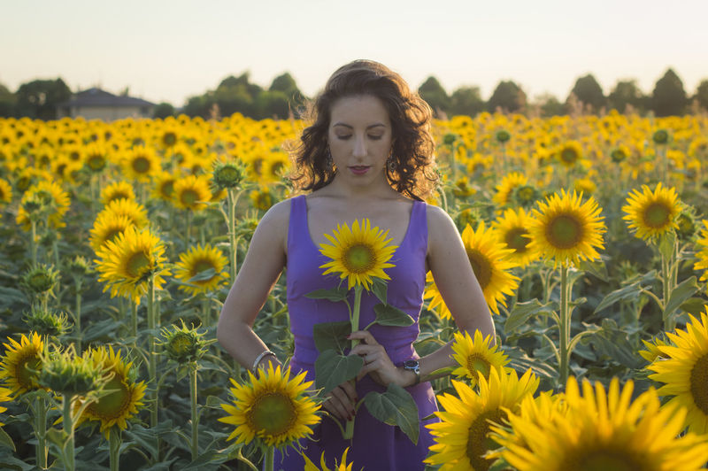 Portrait Of Young Woman Standing Against Sunflower Field