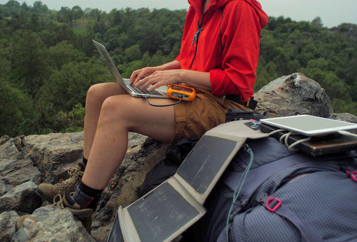 caucasian female hiker sitting on a rock while working on a laptop being charged by solar panels nearby, portable solar charing technology concept Backpacking Camping Charing Cross Freedom Hiking Nature Sitting Solar Panel Tablet Travel Trekking Woman Working Activity Adventure Battery Casual Clothing Communication Connection Day Female Holding Internet Laptop Leisure Activity Lifestyles Men Midsection Nature Navigation One Person Outdoors People Portable Information Device Real People Rock Rock - Object Sitting Solid Surfing The Net Technology Wireless Technology
