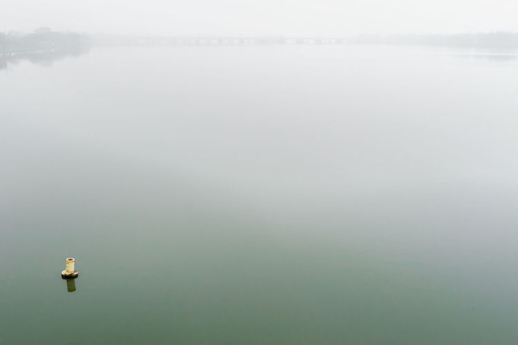 Water measurement gauge in lake during foggy weather